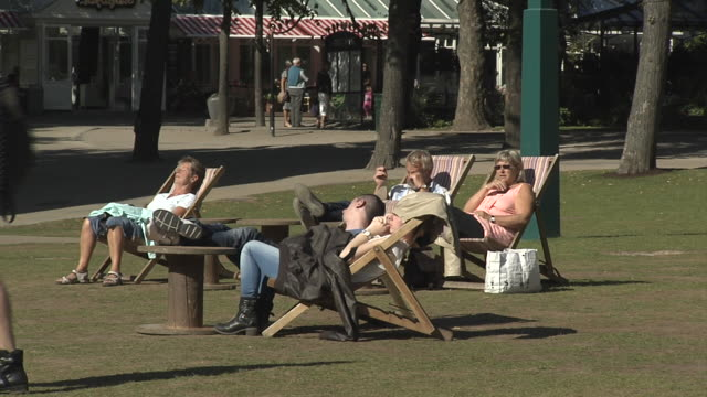 people relax on deckchairs at copenhagen's tivoli gardens. - outdoor chair stock videos & royalty-free footage