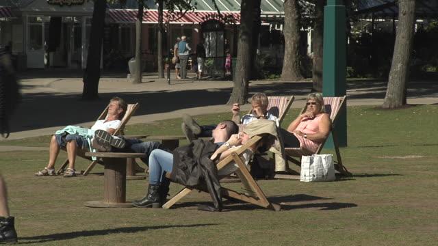 vídeos de stock e filmes b-roll de people relax on deckchairs at copenhagen's tivoli gardens. - apanhar sol