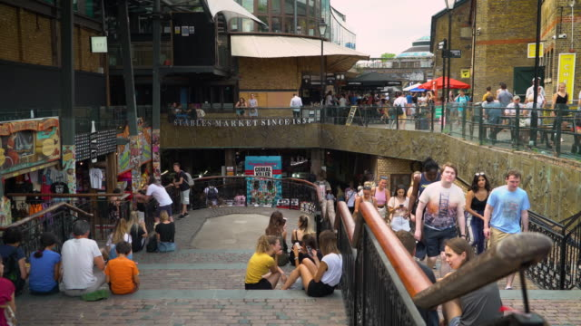 People relax on the steps leading down to Camden's Stables Market, London
