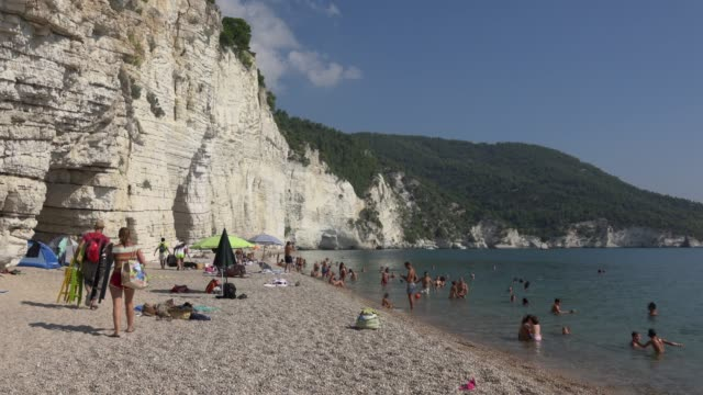 people relax on vignanotica beach with white limestone rocks at the adriatic sea - adriatic sea stock videos & royalty-free footage