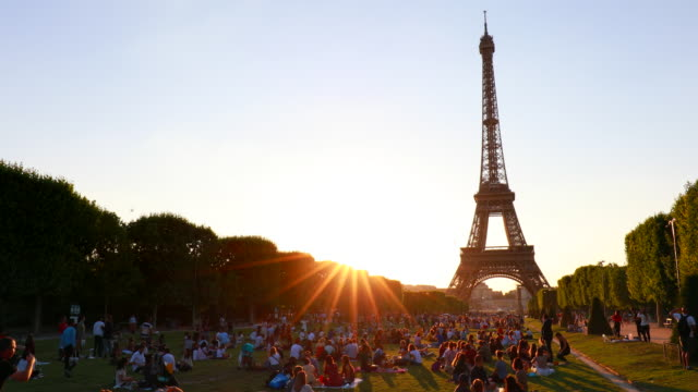 people relaxing at champ de mars at the eiffel tower, tracking left - city break stock videos & royalty-free footage