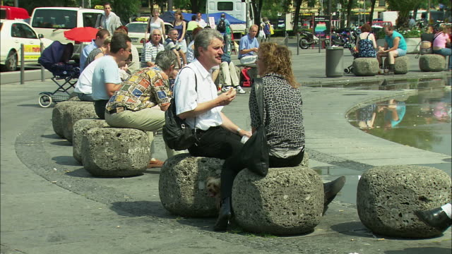 MS People relaxing at fountain in Karlsplatz, Munich, Bavaria, Germany