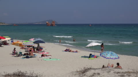 pan / people relaxing at lido di cea beach - large group of people stock videos & royalty-free footage