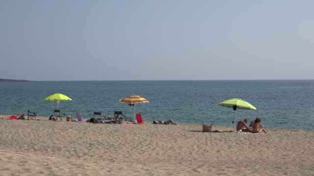 tu / people relaxing at torre di bari beach - sonnenschirm stock-videos und b-roll-filmmaterial