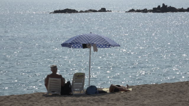 people relaxing at torre di bari beach - sonnenschirm stock-videos und b-roll-filmmaterial