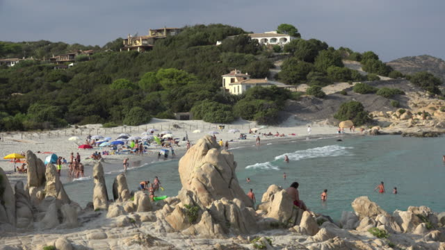 pan / people relaxing at villasimius beach - spiaggia stock videos & royalty-free footage
