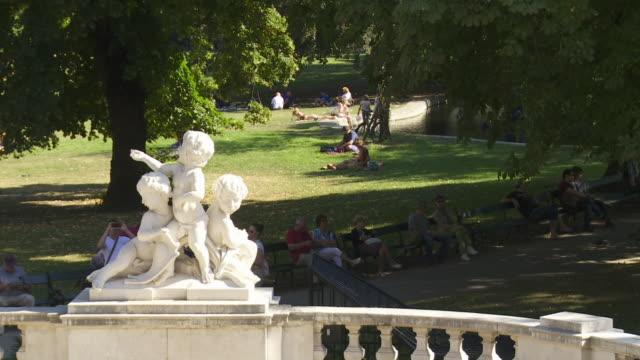 people relaxing in burggarten garden in vienna - figura maschile video stock e b–roll