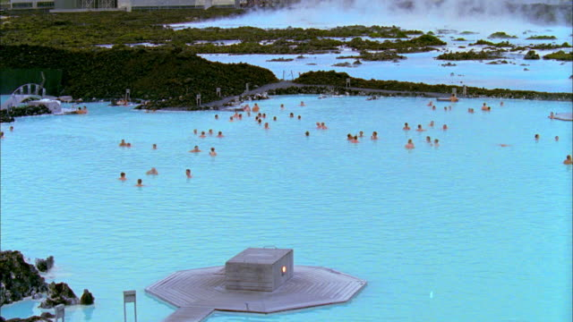 WS TU People relaxing in hot spring, Svartsengi Geothermal Plant in background, Blue Lagoon, Grindavik, Iceland