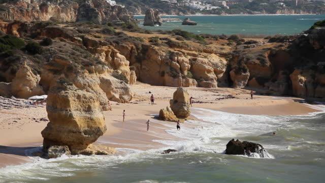 stockvideo's en b-roll-footage met ws ha people relaxing in ocean waves on praia de sao rafael / algarve, portugal - geërodeerd