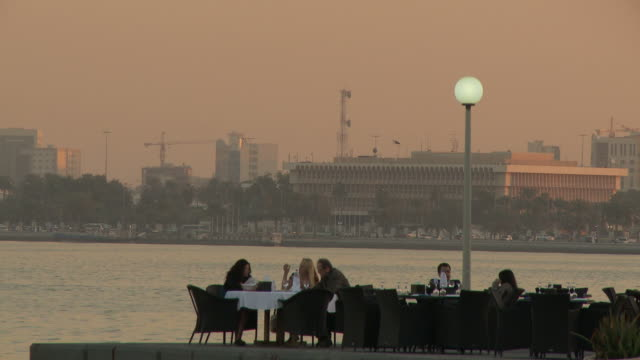 ws people relaxing in outdoors cafe by bay at dusk / doha, qatar - doha stock videos & royalty-free footage