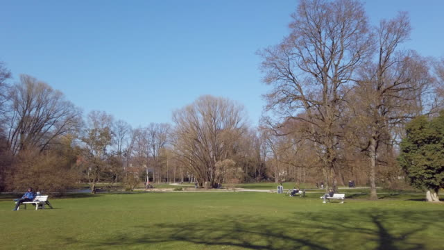 people relaxing in public park during coronavirus pandemic - march month stock videos & royalty-free footage