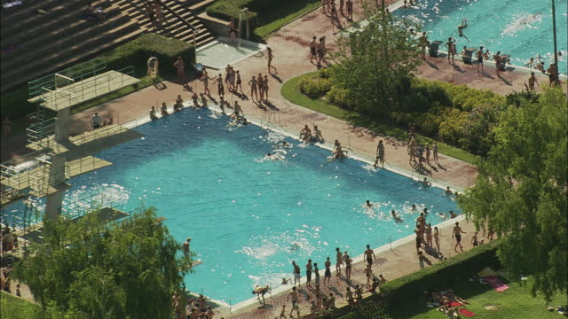AERIAL People relaxing in swimming pool, Wurzburg, Bavaria, Germany