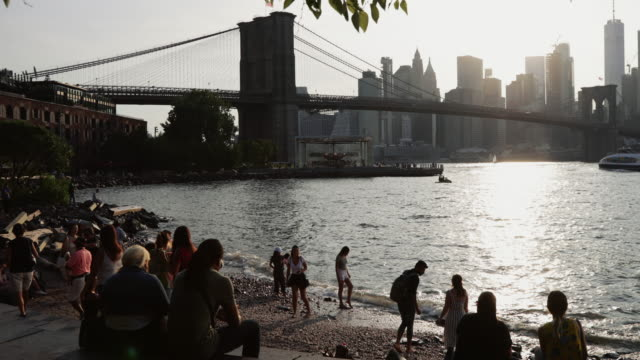 vidéos et rushes de people relaxing in the main street park on the east river in dumbo in brooklyn new york with view of the brooklyn bridge and the manhattan skyline - pont de brooklyn