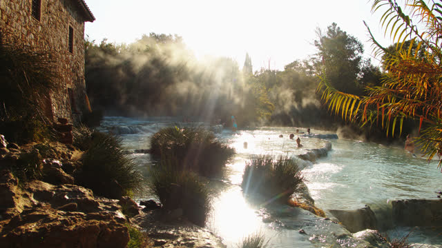 slo mo people relaxing in thermal waters of the saturnia hot springs - natural landmark stock videos & royalty-free footage