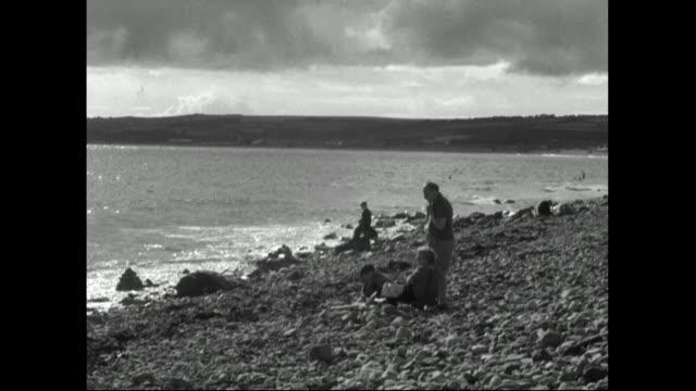 vídeos y material grabado en eventos de stock de people relaxing on a stony beach in cornwall;1951 - cornwall inglaterra