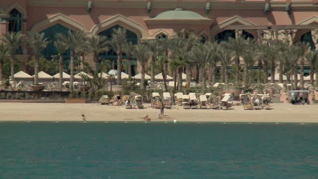 vidéos et rushes de ws people relaxing on beach at atlantis resort in dubai / dubai, united arab emirates - palace