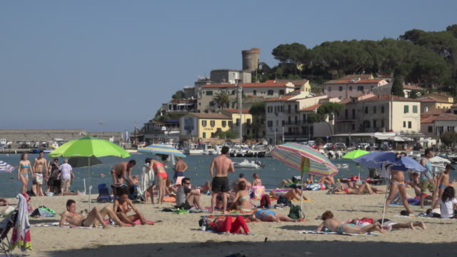 pan / people relaxing on beach at marina di campo - island of elba stock videos & royalty-free footage