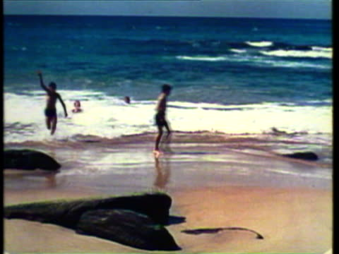 1953 ws ms people relaxing on beach / australia / audio - audio available stock videos & royalty-free footage