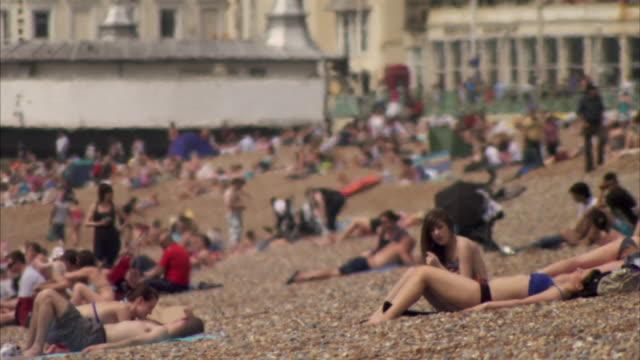 CU, people relaxing on beach / Brighton Beach, England
