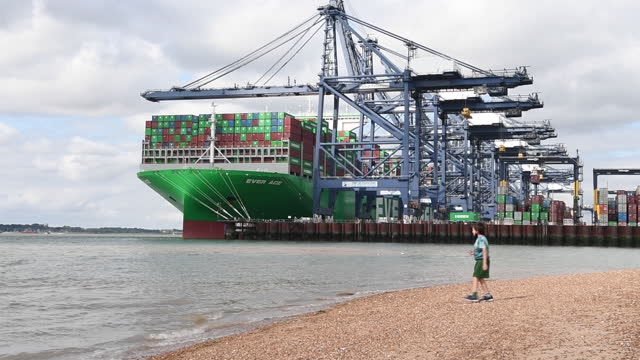 people relaxing on beach in area of port of felixtowe, with world's largest container ship, ever ace being loaded, in felixstowe, suffolk, england,... - western script stock videos & royalty-free footage