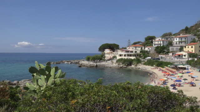 pan / people relaxing on beach of seccheto - island of elba stock videos & royalty-free footage