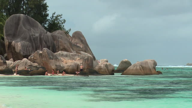 WS People relaxing on beach with rock formations, Seychelles
