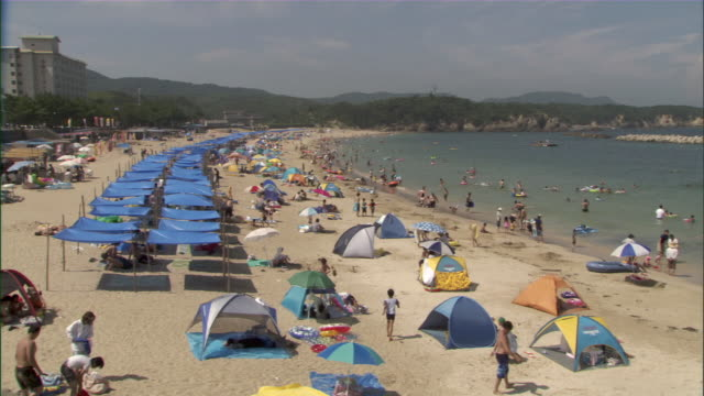 WS People relaxing on beach with tents and sun shades / Oma, Aomori Prefecture, Japan