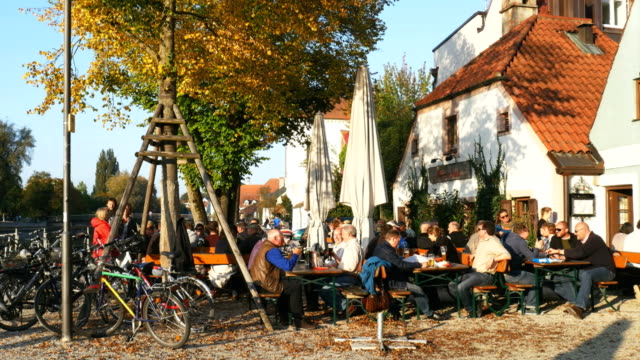 pan people relaxing on isar river bank in landshut - pavement cafe stock videos & royalty-free footage