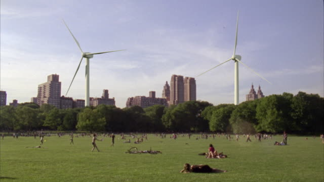 ws people relaxing on lawn in central park, wind turbines and skyscrapers in background / new york city, new york, usa - geographical locations stock videos and b-roll footage