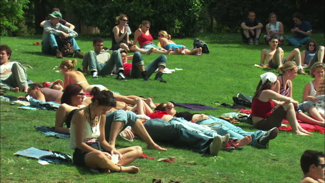 ws people relaxing on lawn in retiro park, madrid, spain - sonnenbaden stock-videos und b-roll-filmmaterial
