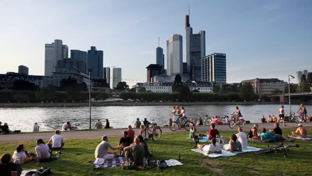 WS People relaxing on riverbank, Commerzbank Tower and skyscrapers in background / Frankfurt, Hessen, Germany