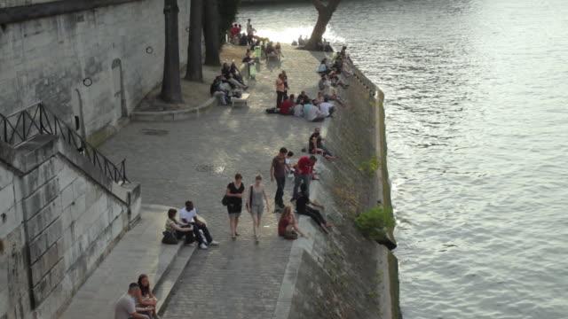 ws tu people relaxing on riverbank, quai de bourbon, ile saint-louis, paris, france - saint louis bildbanksvideor och videomaterial från bakom kulisserna