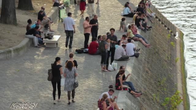 ws tu people relaxing on riverbank, quai de bourbon, ile saint-louis, paris, france - seine river stock videos and b-roll footage