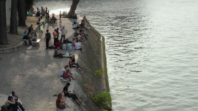 ws ha people relaxing on riverbank, quai de bourbon, ile saint-louis, paris, france - saint louis bildbanksvideor och videomaterial från bakom kulisserna