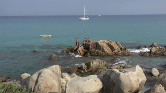 people relaxing on rock formation at villasimius beach - spiaggia stock videos & royalty-free footage