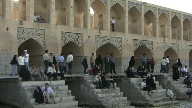 MS People relaxing on steps at Khaju Bridge on Zayandeh River, Isfahan, Iran