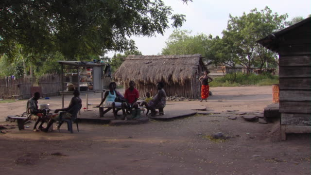 ws people relaxing on yard outside grass huts tamale, ghana - 草葺小屋点の映像素材/bロール