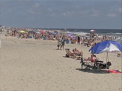 ls of people relaxing under umbrellas and others walking along the beach in point pleasant new jersey point pleasant beach has both public access and... - ocean avenue stock videos & royalty-free footage