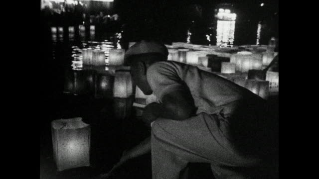people releasing paper lanterns on hiroshima river; 1966 - sad old asian man stock videos & royalty-free footage