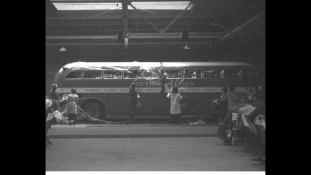 People remove cellophane wrap from new streamlined Greyhound bus as audience looks on at unveiling ceremony at Convention Hall / bus stands at curb...