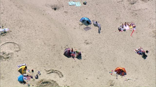 vídeos de stock, filmes e b-roll de ws aerial pan  people resting in beach tent at beach  / north frisian seast peter -ording,  schleswig-holstein, germany - toalha de praia