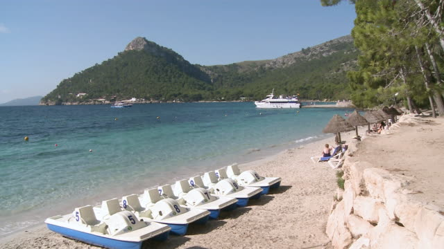 ms people resting on beach / pollenca, mallorca, spain  - paddle boat stock videos & royalty-free footage