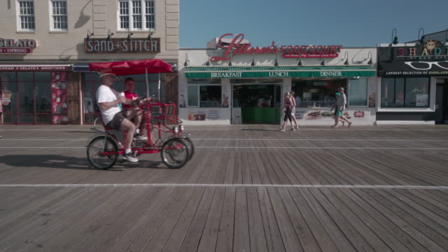 vídeos y material grabado en eventos de stock de people ride a bike surry down the ocean city boardwalk in the morning. - bulevar