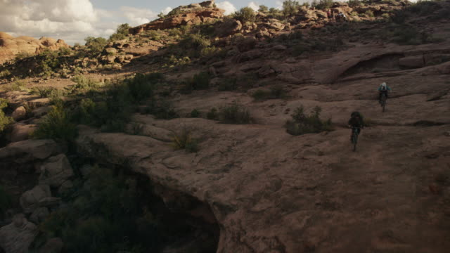people ride bikes through scenic utah mountains, aerial - canyon stock-videos und b-roll-filmmaterial