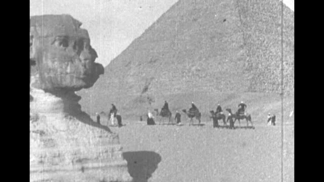 people ride camels, run near the giza pyramids / line of camel riders between sphinx in foreground and pyramid in background / montage sphinx, with... - archaeologist stock videos & royalty-free footage