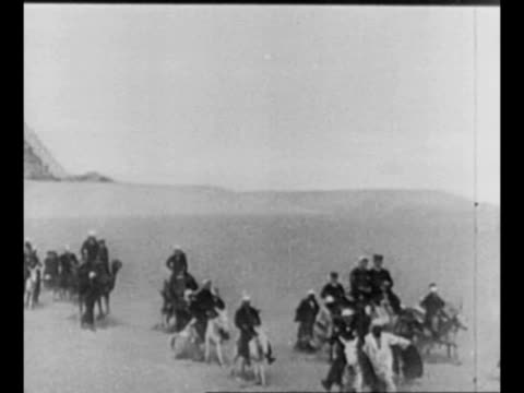 people ride camels run near the giza pyramids / line of camel riders between sphinx in foreground and pyramid in background / montage sphinx with... - 1910 1919 stock-videos und b-roll-filmmaterial