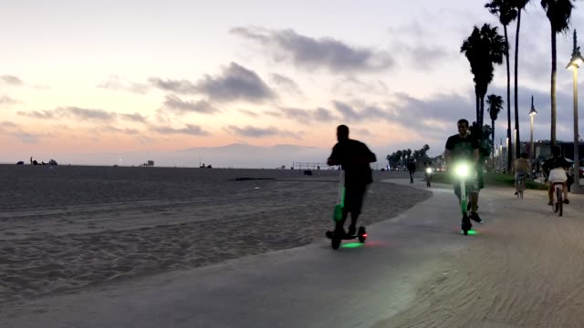 people ride escooters along venice beach on august 13 2018 in los angeles california shared escooter startups bird and lime have rapidly expanded in... - push scooter stock videos and b-roll footage