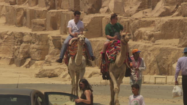 People ride on camels next to one of Giza's ancient pyramids, Egypt.