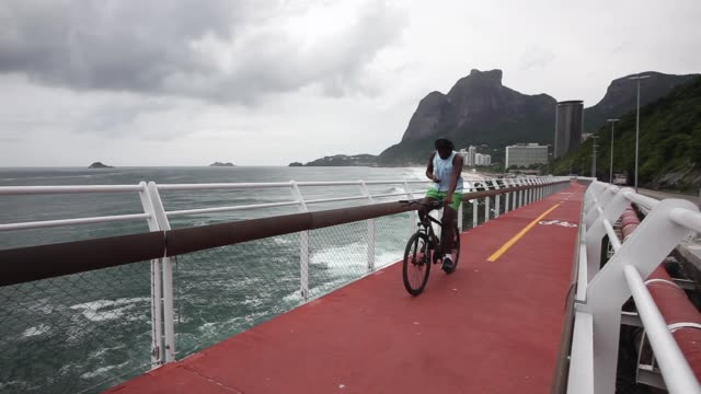 people ride on the city's new people ride on the new avenida niemeyer bicycle lane which hugs the atlantic coastline on the day it was inaugurated on... - avenida stock videos & royalty-free footage