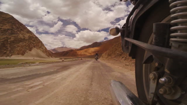 6 people ride royal enfield motorcycles on a tiny country road in the rocky landscape of leh, india - royal blue stock videos & royalty-free footage